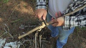 O caminhante corta um ramo de árvore no close-up filme