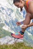 O caminhante da jovem mulher que amarra a bota ata, altamente nas montanhas Imagens de Stock Royalty Free
