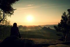 O caminhante da jovem mulher toma uma árvore do fole do resto no pico da montanha e aprecia a aurora do outono Fotografia de Stock Royalty Free