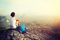 O caminhante da mulher aprecia a vista no penhasco do pico de montanha Fotos de Stock Royalty Free
