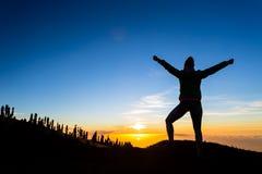O caminhante da mulher com os braços estendido aprecia montanhas Fotografia de Stock
