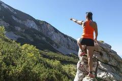 O caminhante da mulher mostra o pico de montanha Fotos de Stock