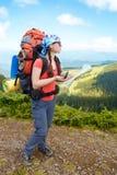 O caminhante da mulher nas montanhas determina o sentido Imagens de Stock