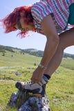 O caminhante da mulher que amarra a bota ata, altamente nas montanhas imagem de stock royalty free