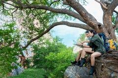 O caminhante das mulheres do grupo com a trouxa em verificações grandes da árvore traça para encontrar sentidos e olhar binóculos fotografia de stock royalty free