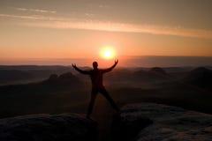 O caminhante de salto no preto comemora um triunfo entre dois picos rochosos Aurora maravilhosa com o sol acima da cabeça Fotos de Stock Royalty Free