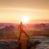 O caminhante de salto no preto comemora um triunfo entre dois picos rochosos Aurora maravilhosa com o sol acima da cabeça Foto de Stock