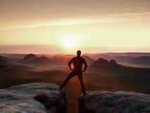 O caminhante de salto no preto comemora um triunfo entre dois picos rochosos Aurora maravilhosa com o sol acima da cabeça Fotografia de Stock