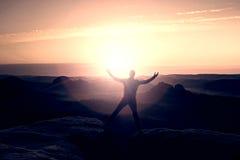 O caminhante de salto no preto comemora um triunfo entre dois picos rochosos Aurora maravilhosa com o sol acima da cabeça Fotos de Stock