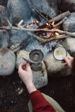 O caminhante derrama pr?prio do homem o caf? quente pr?ximo ? fogueira Assento masculino e guardar de uma caneca de caf? ap?s a c imagens de stock royalty free