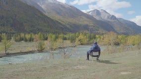 O caminhante do homem relaxa aprecia a natureza em um banco de rio na estação do inverno do outono das montanhas video estoque