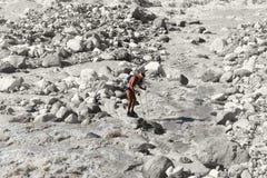 O caminhante está em uma rocha no meio de um rio raging da montanha imagens de stock royalty free