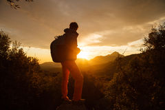 O caminhante está no penhasco sobre o nascer do sol Fotos de Stock Royalty Free