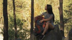 O caminhante fêmea senta-se na rocha video estoque