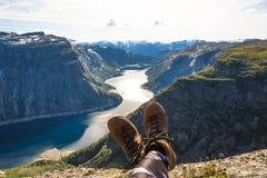 O caminhante feliz relaxa em Trolltunga A juba aprecia o lago bonito e o bom tempo em Noruega Imagens de Stock Royalty Free