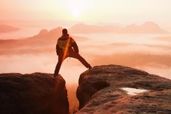 O caminhante no preto está saltando entre os picos rochosos Aurora maravilhosa em montanhas rochosas, névoa alaranjada pesada no  Imagens de Stock Royalty Free