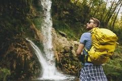 O caminhante novo parou ao lado de uma cachoeira da montanha para descansar imagem de stock