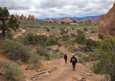 O caminhante que anda abaixo de uma fuga nos diabos jardina no parque nacional dos arcos em Moab Utá Foto de Stock