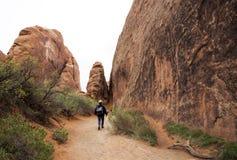 O caminhante que anda abaixo de uma fuga nos diabos jardina no parque nacional dos arcos em Moab Utá Fotografia de Stock