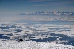 O caminhante que olha Tatra repica acima das planícies nevado na névoa no Polônia foto de stock