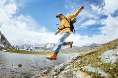 O caminhante salta da rocha grande contra o lago das montanhas Imagem de Stock Royalty Free