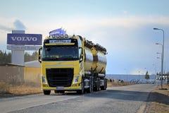 O caminhão de tanque amarelo de Volvo FH na estrada com Volvo transporta o sinal Foto de Stock