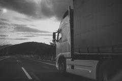 O Camion, camionete monta ao longo da estrada na noite, vista traseira a camionete do argo, caminhão, kamion transporta bens ou a fotos de stock