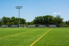 O campo de futebol com bancada e a luz estão em um dia ensolarado fotos de stock