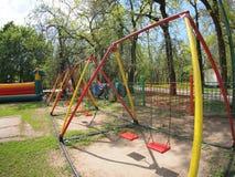 O campo de jogos das crianças com balanços no parque imagens de stock royalty free
