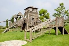 O campo de jogos das crianças feito da madeira no parque Imagem de Stock
