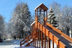 O campo de jogos das crianças no inverno, a corrediça das crianças imagem de stock