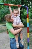 O campo de jogos, o menino estava pendurando na barra, e em minha mãe HU Imagens de Stock Royalty Free