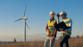 O campo ensolarado com um moinho de vento está obtendo cruzado por dois especialistas de fala Conceito limpo, eco-amigável da ene vídeos de arquivo