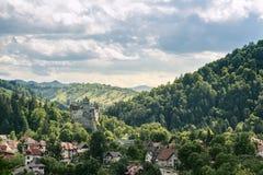 O campo negligencia a vista das casas e do castelo sobre os montes no verão foto de stock royalty free