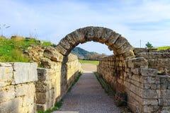 O campo onde os Olympics originais foram guardados vistos com as ruínas do arco através de que os atheletes gregos correram em Ol imagens de stock