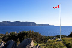 O Canada!. Canada's maple leaf flag flies majestically at the Lobster Cove Head Lighthouse harbor entrance near Rocky Harbour, Newfoundland and Labrador royalty free stock photo