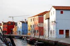 O canal e as casas coloridas iluminaram-se pelo sol de ajuste na área Itália de Burano Veneza Foto de Stock