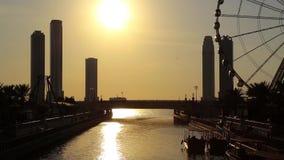 O canal e os ferris de Al Qasba rodam dentro a cidade de Sharjah, Emiratos Árabes Unidos Por do sol filme