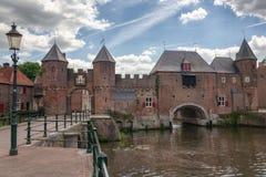 O canal Eem com no fundo a porta medieval o Koppelpoort na cidade de Amersfoort nos Países Baixos imagens de stock