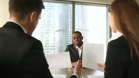 O candidato africano bem sucedido contratou após a entrevista de trabalho, aperto de mão, assinando papéis filme