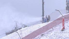 O canhão da neve derrama a neve na inclinação do esqui filme