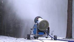 O canhão da neve derrama a neve na inclinação do esqui