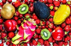 O canhão, o quivi, o abacate, o pêssego e um dragão frutificam entre bagas das morangos e de cerejas doces foto de stock royalty free