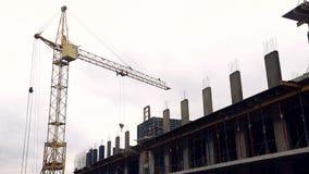 O canteiro de obras tem trabalhadores e um guindaste de construção video estoque