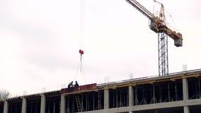 O canteiro de obras tem trabalhadores e um guindaste de construção filme