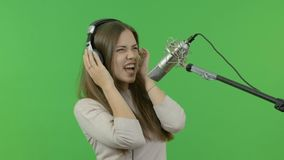 O cantor bonito é muito expressivo canta no microfone do estúdio Em um fundo verde video estoque
