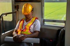O capacete de segurança vestindo do coordenador asiático cansado cai adormecido durante horários laborais no trem imagem de stock royalty free