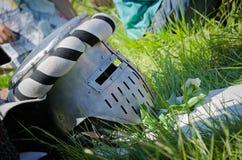 O capacete medieval do ferro do cavaleiro encontra-se na grama Fotografia de Stock