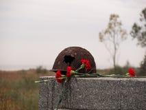 O capacete militar oxidado velho com um furo grande encontra-se no memorial ao lado de um ramalhete de cravos vermelhos contra o  Fotografia de Stock
