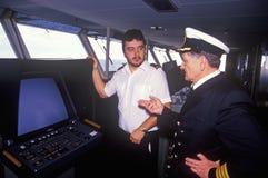 O capitão da balsa Bluenose e um membro do grupo que está antes de um instrumento na ponte foto de stock royalty free